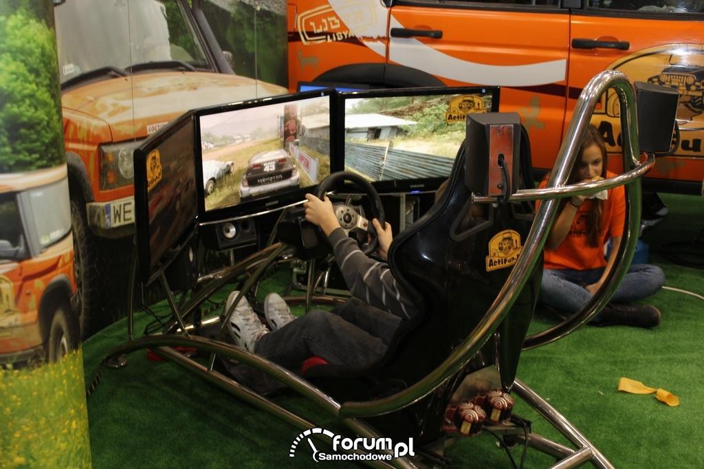Symulator z fotelem, kierownicą i peadłami do gry