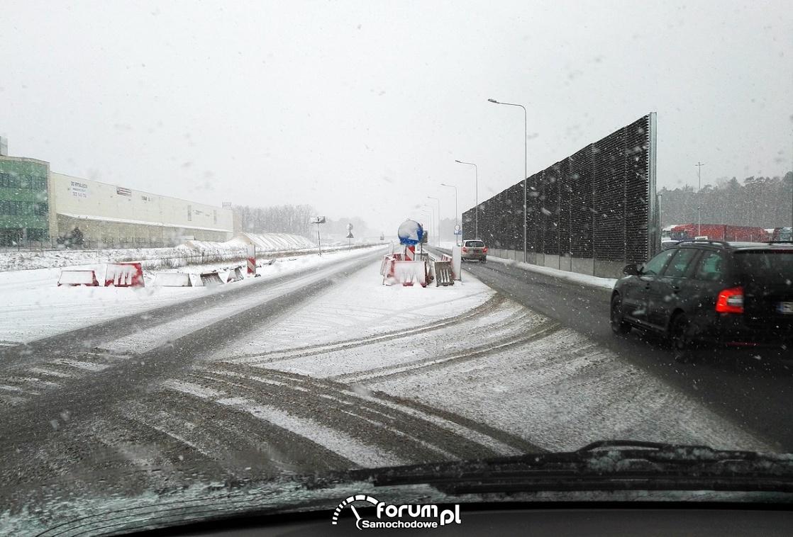 Droga, padający śnieg, tymczasowa wysepka