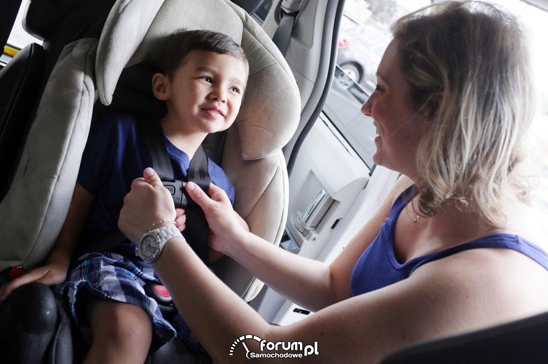 Dziecko w zapiętych pasach w foteliku samochodowym