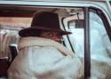 Kobieta w kapeluszu i grubej kurtce w samochodzie