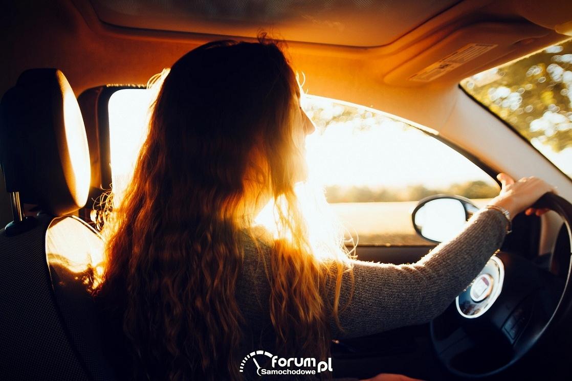 Kobieta z kierownicą, zachodzące słońce