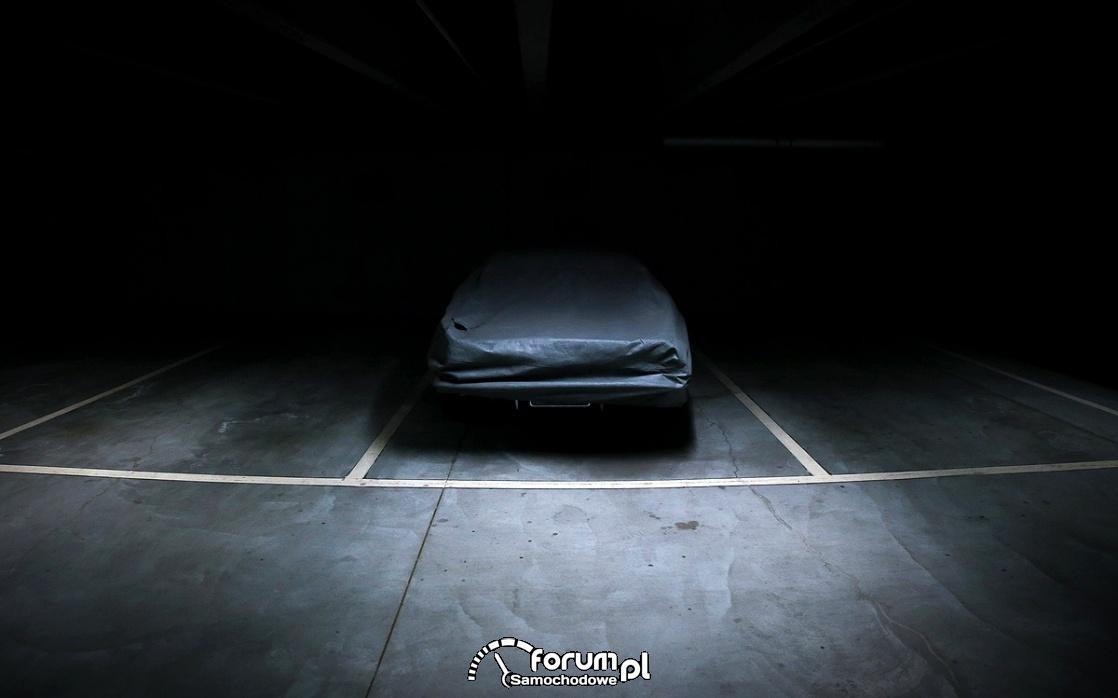 Pokrowiec na samochód, auto przykryte pokrowcem na parkingu