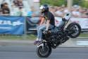 Jazda na motorze w pozycji siedzącej na baku na przednim kole z nogami do przodu