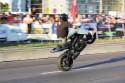 Jazda na motorze w pozycji siedzącej na baku na tylnym kole z nogami do przodu
