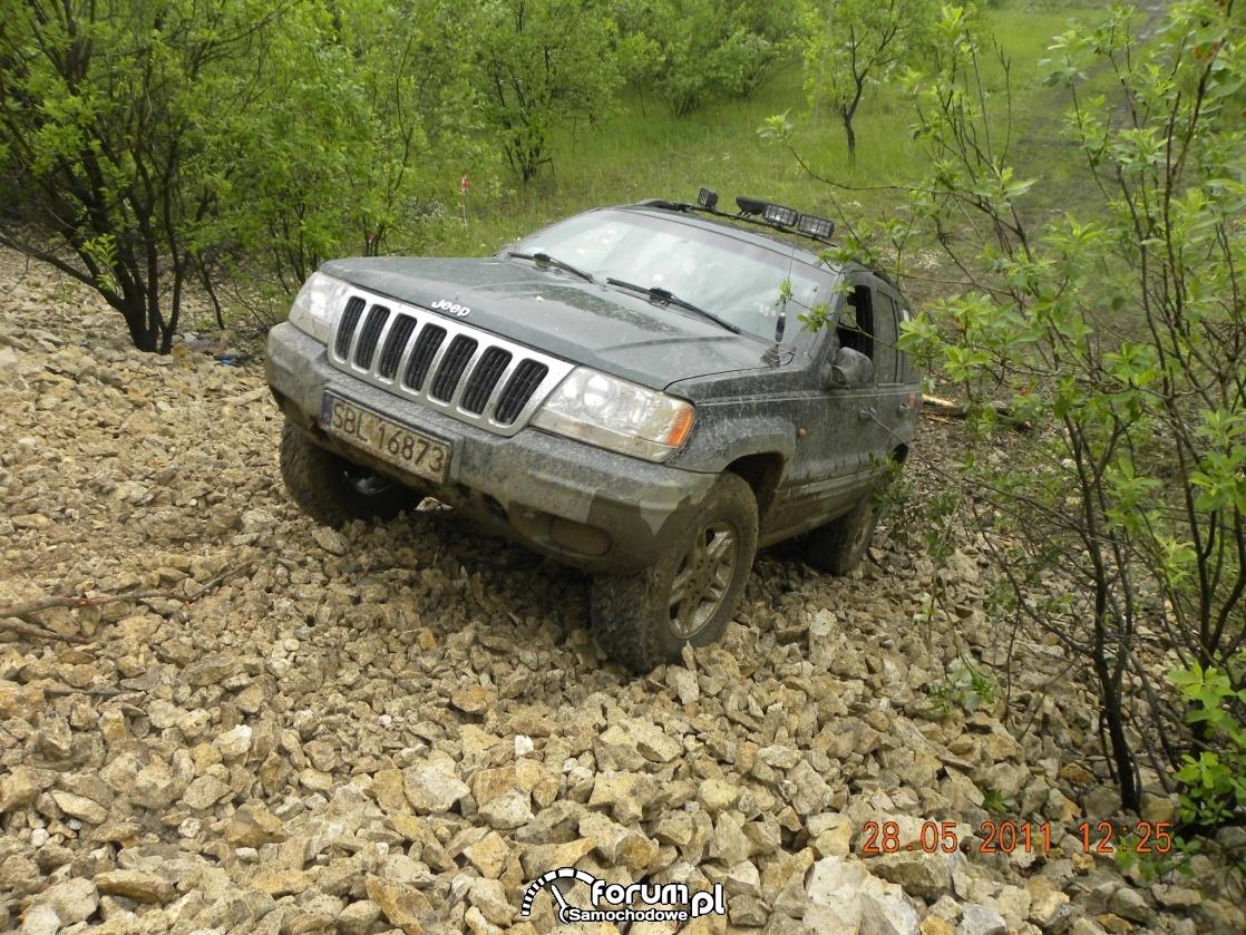 Jeep Grand Cherokee wjeżdża po stromym kamienistym zboczu